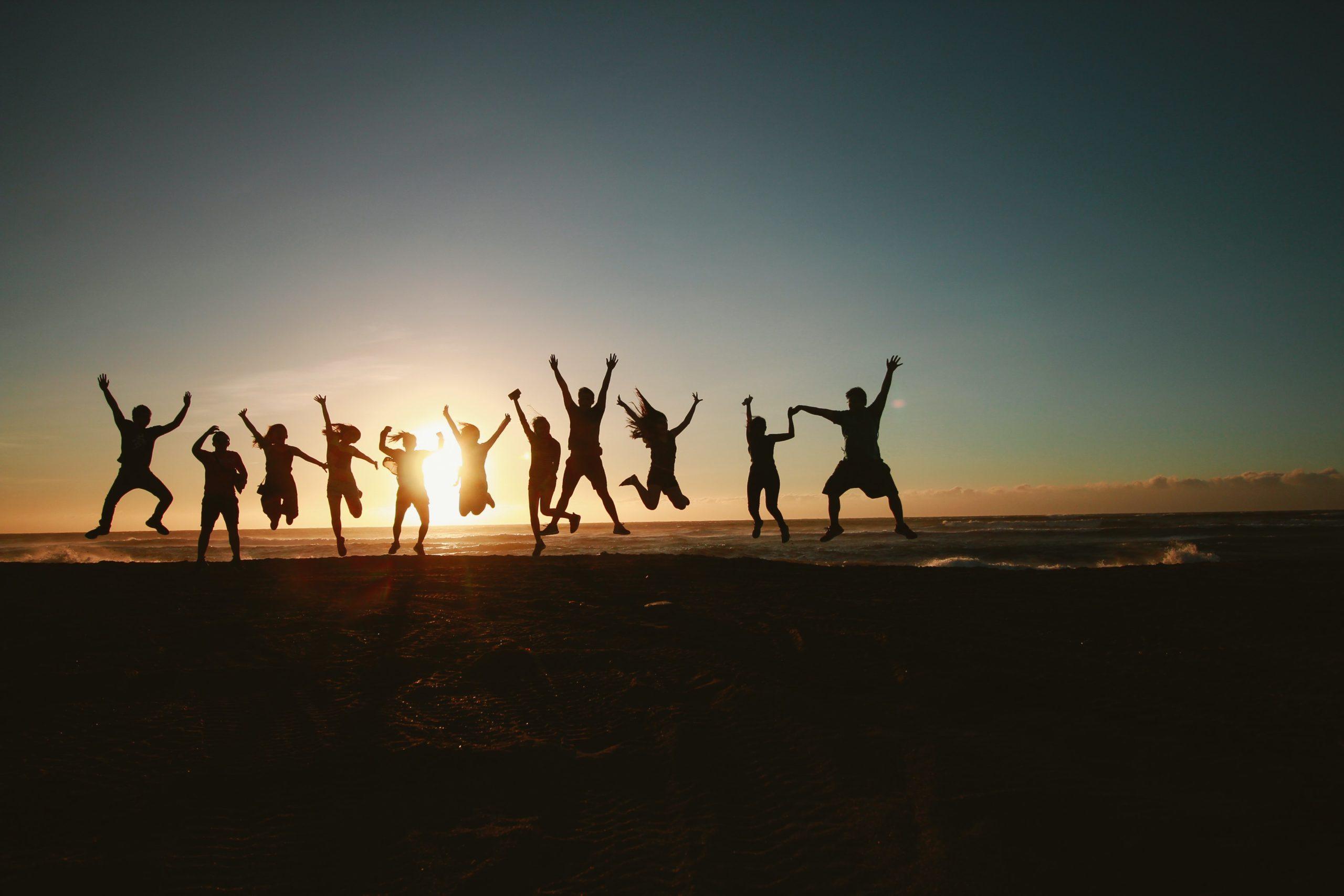 En grupp människor som hoppar framför en sol.