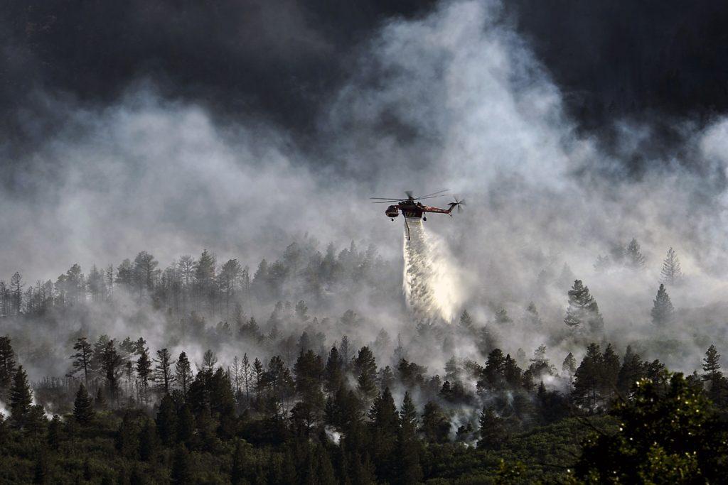 En helikopter släpper vatten över en brand i en skog.