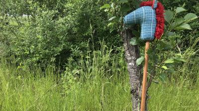 Foto på en käpphäst som står lutad mot ett träd.