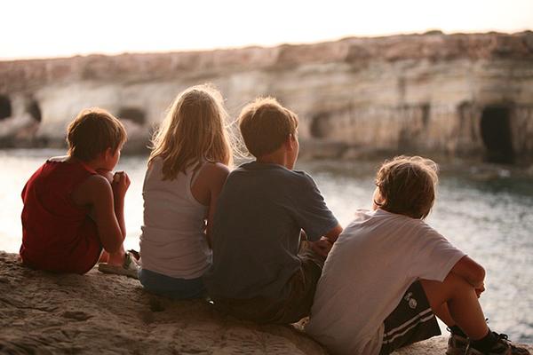 Fyra vänner som sitter vid en sjö. Personerna på bilden har inget med texten att göra.