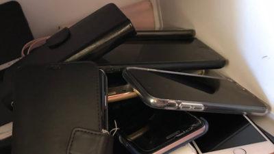 Foto på en hög med mobiltelefoner i ett skåp.