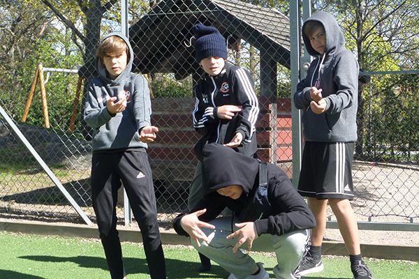 Fyra killar poserar på en fotbollsplan.