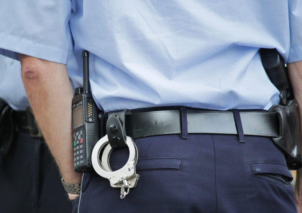 Polis med pistol och handbojor