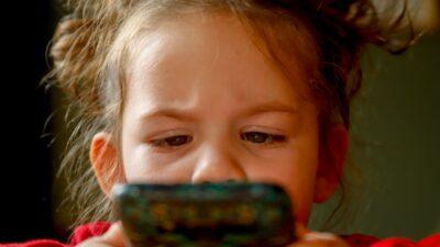 Flicka som tittar på telefonen.