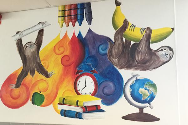 En färgglad väggmålning med bland annat en jordglob, sengångare och en klocka.