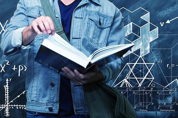 En person som bläddrar i en tjock bok framför en svart tavla med mattetal på.
