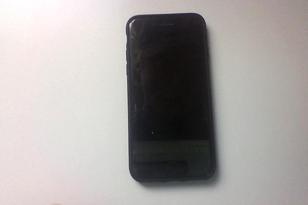 Foto på en svart mobiltelefon som ligger på ett vitt bord.