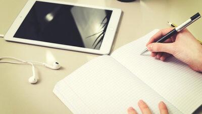 En elever skriver i en bok. På bänken framför ligger en läsplatta med ikopplade hörlurar.