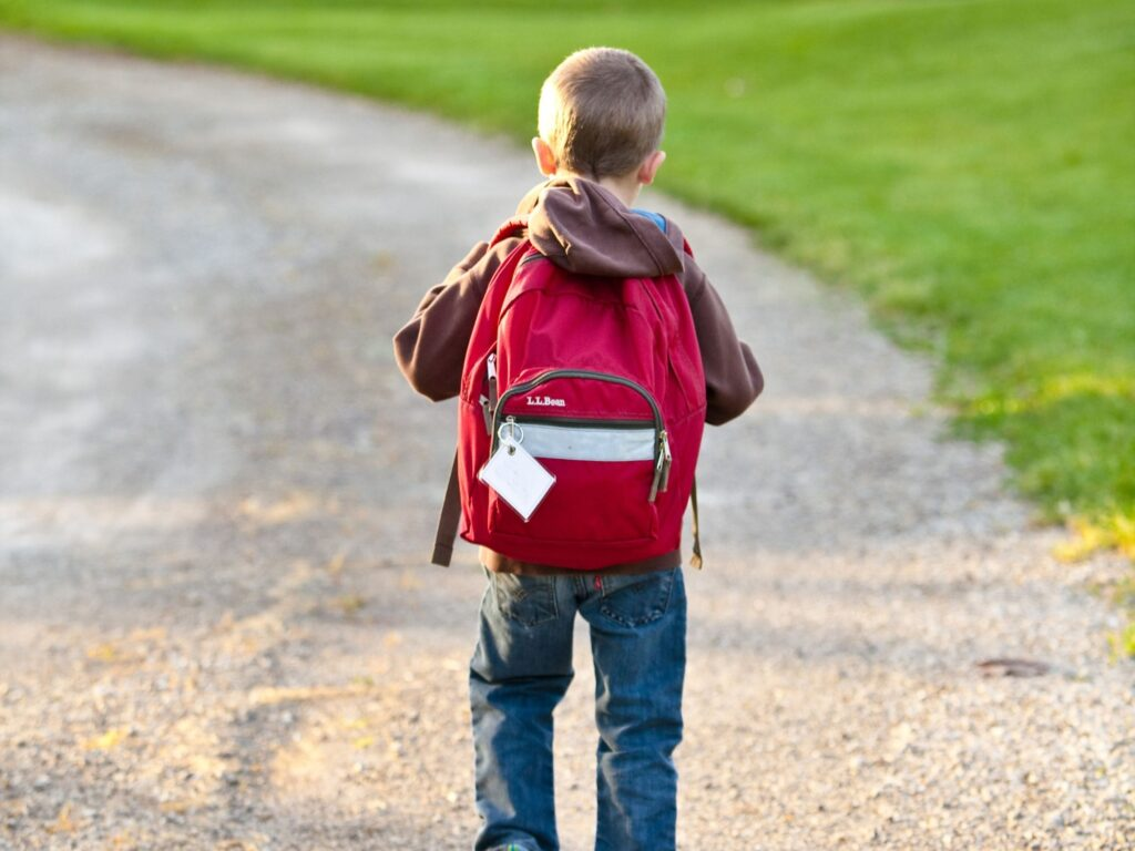 En pojke med en ryggsäck på ryggen.