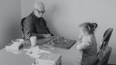 En äldre man och en flicka spelar spel