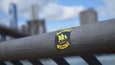 Ett klistermärke där det står Refugees welcome