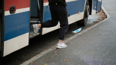 Person som går av en buss.