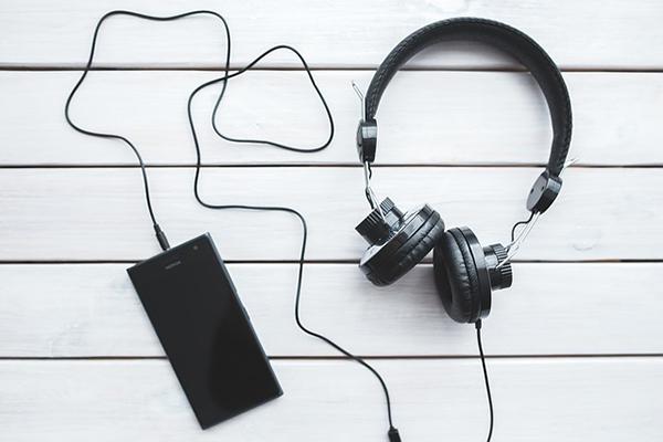 En smartphone som är kopplad till ett par hörlurar.