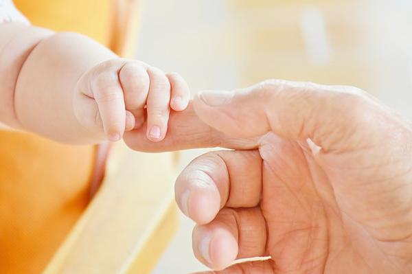 En bebishand som håller i en vuxenhand.