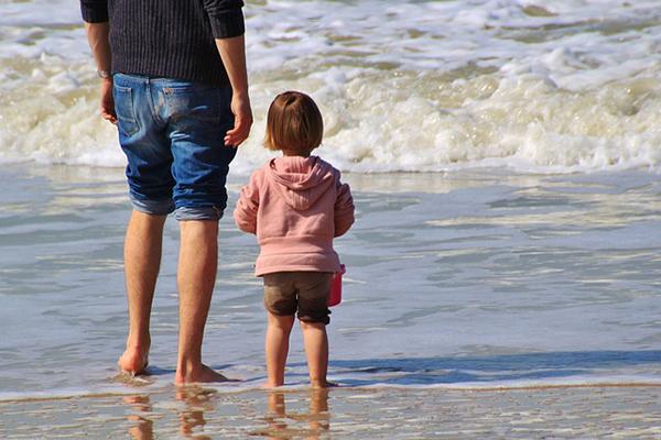 En pappa med sin dotter. De tittar på havet.