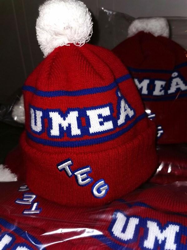 Röda mössor som det står Umeå och Teg på.