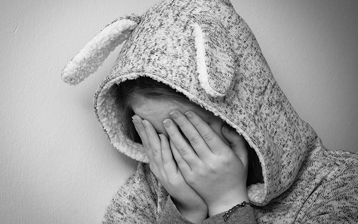 Ett barn som gömmer ansiktet i händerna.
