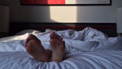 Foto på ett par fötter som sticker ut ur täcket.