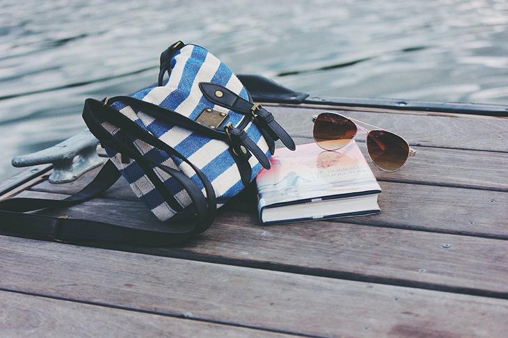 En väska, bok och ett par solglasögon som ligger på en brygga.