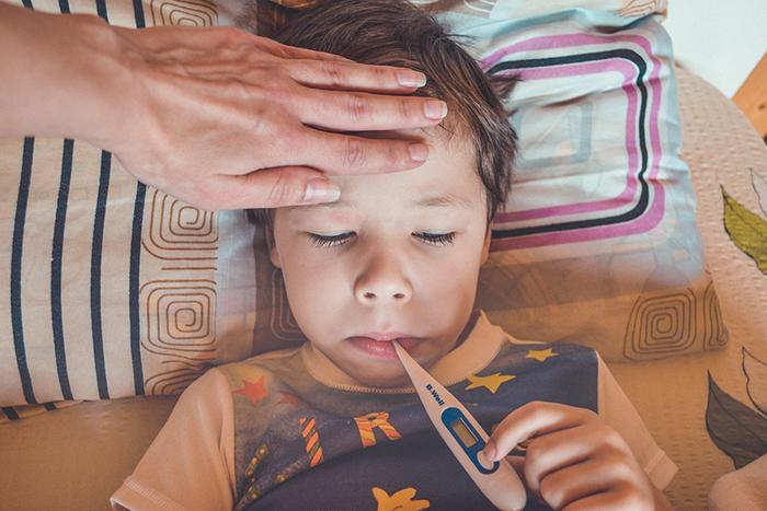 En pojke som har en termometer i munnen och en hand på sin panna.