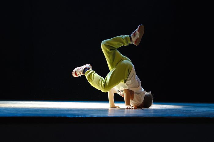 En hiphop-dansare som står på huvudet i en dans.