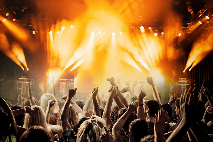 Människor som står samlade framför en stor scen. Strålkastarna lyser och publiken håller upp sina händer.