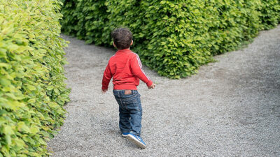 En liten pojke som precis ska springa in i en labyrint av buskar.