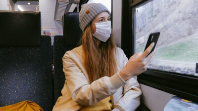Tjej på tåg med munskydd