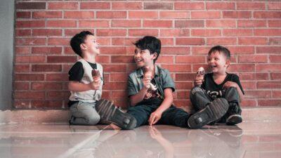 Tre pojkar äter glass och skrattar