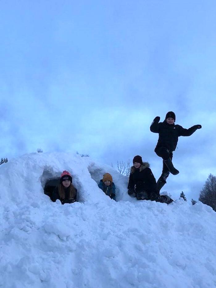 En stor snöhög med fyra elever som tittar fram ur gångarna i den.
