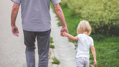 En äldre person som håller ett barn i handen.