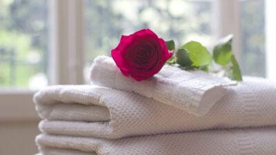En hög med vikta handdukar och en röd ros som ligger överst.