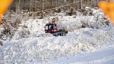 En röd pistmaskin som kör i en snöig backe.