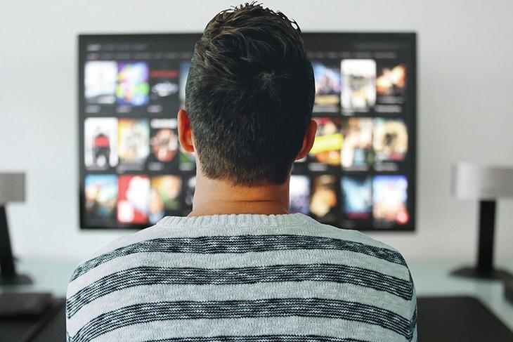 En person som sitter framför en tv och ska välja film.