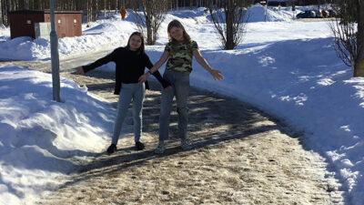 Solen skiner och två elever som står bland snöhögarna utan jackor.