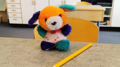 Ett foto på ett färgglatt kramdjur som sitter på en skolbänk.