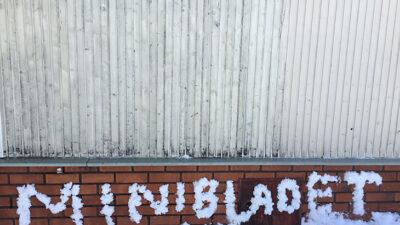På en tegelvägg står det MINIBLADET i snöskrift.