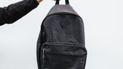 En hand som håller i en ryggsäck