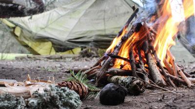 Foto på ett läger. I förgrunden brinner en brasa och i bakgrunden står det ett grönt tält.