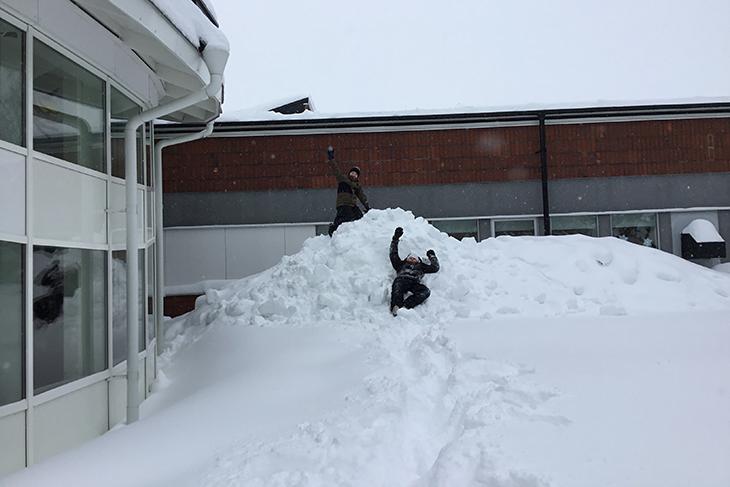 Två elever som leker i en stor snöhög.