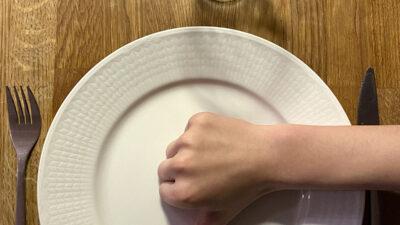 En tom tallrik med en hand på som gör tummen ner.