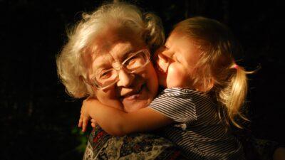 En flicka som kramar om en äldre kvinna