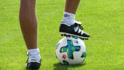 I bild syns två ben och en fotboll på en gräsplan.