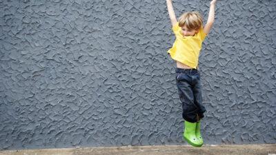 Barn som hoppar framför en grå vägg.