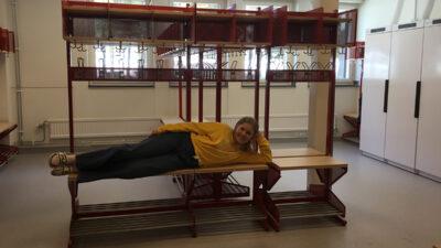 En elev som ligger på en av bänkarna i kapprummet.