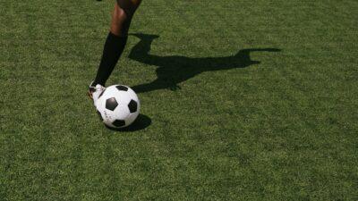 En person som sparkar på en fotboll