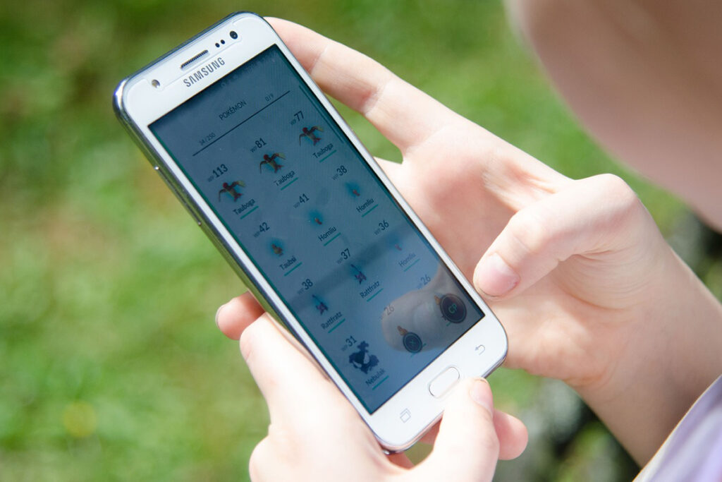 Närbild på en person som spelar Pokémon Go via sin mobiltelefon.