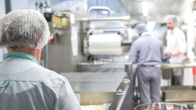 Foto inifrån ett storkök. Människor i vita rockar och hårnät lagar mat.