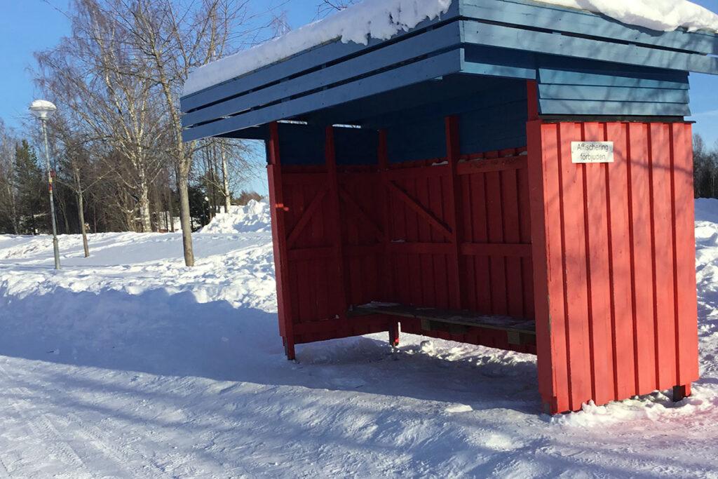 Foto på en röd busskur i ett snölandskap.
