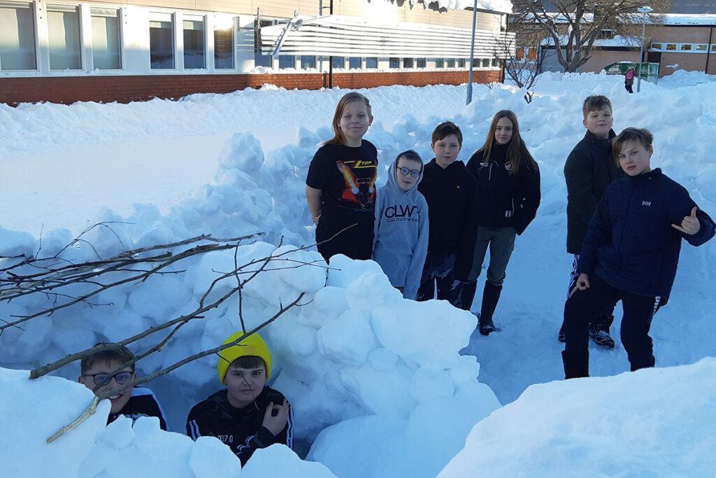Elever från Pitholmsskolan som står i snön vid sin snöborg.